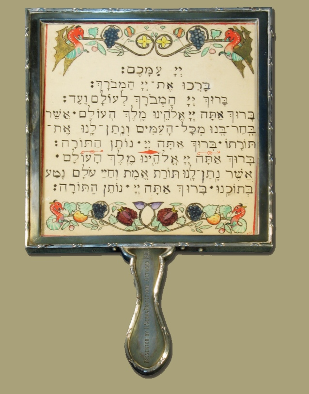 "Silver gilt framed ""blessing"" tablet with handle, ribon and reed border, and engraved presentation inscription by H Sebag-Montefiore, 17.8cm by 15.8cm"